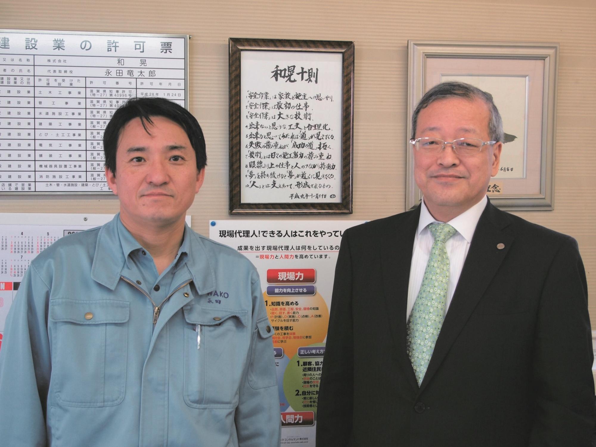 「和晃十則(社員心得)」の前で永田社長と弊社の代表と記念撮影